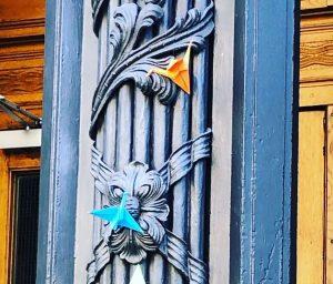zwei bunte Origami Kraniche hängen an einer Säule des Landgerichtes Berlin