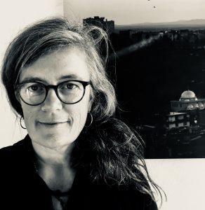 Auf dem Schwarz-weiß Bild ist Christina Clemm. Sie trägt eine Brille und lächelt frontal in die Kamera.